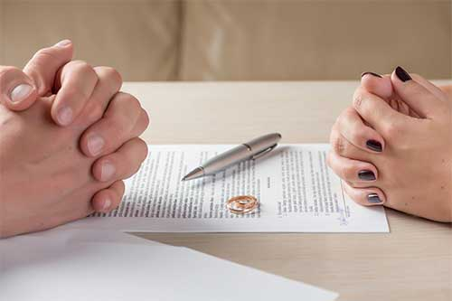 Man and Woman with contract inbetween and wedding ring on top